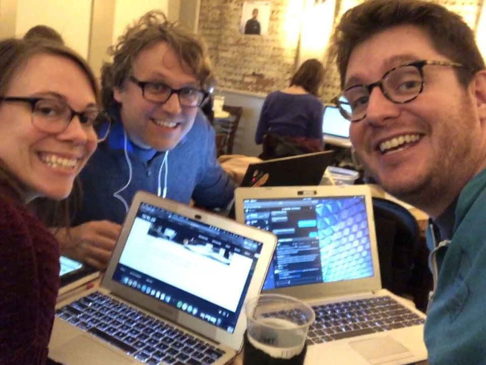3 HWC NYC attendees, hunched over their laptops, smile at the camera