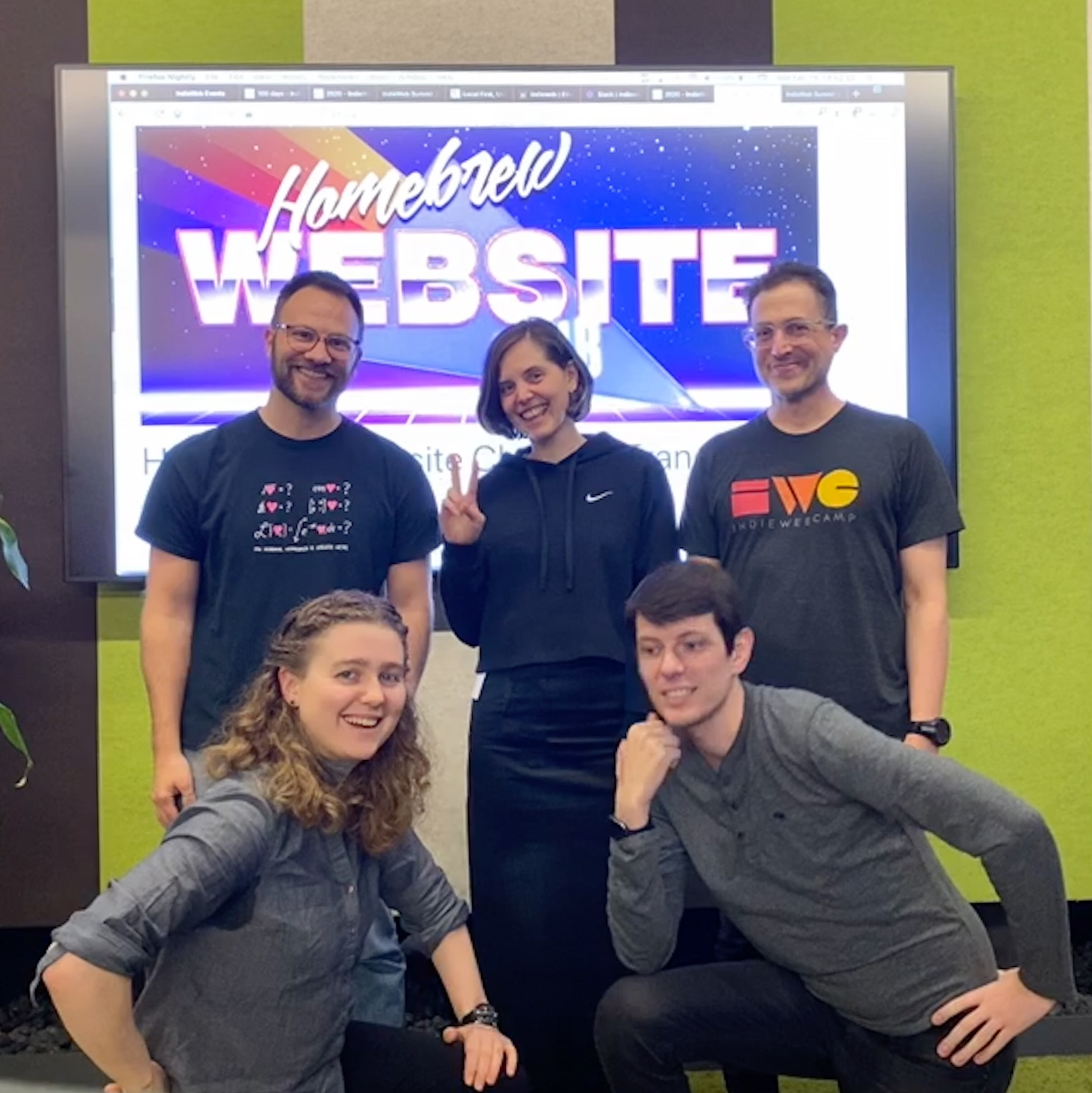 John, Katherine, Tantek, Alex, and Andre at Homebrew Website Club San Francisco, standing in front of a screen with the 1980s style graphic of the Homebrew Website Club.
