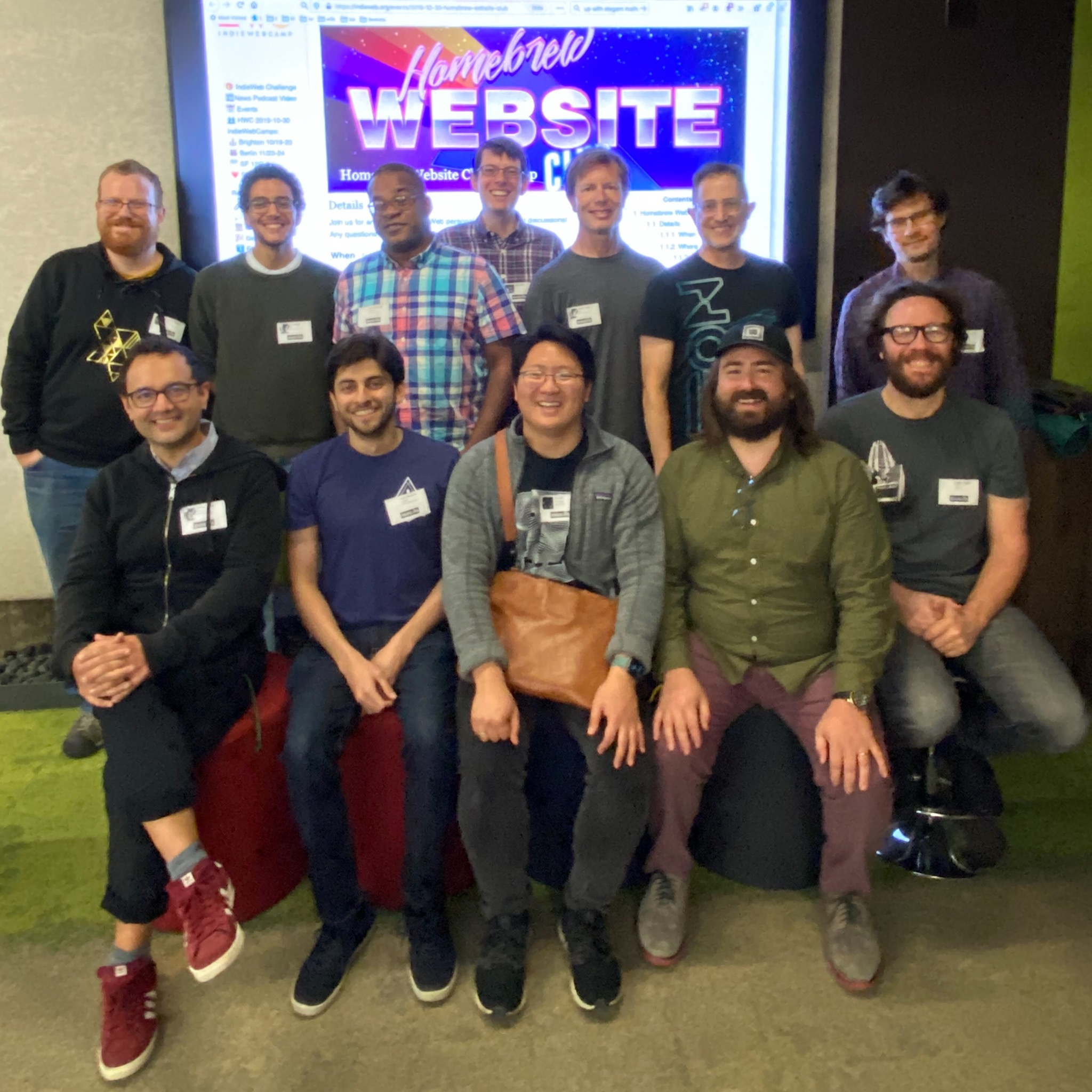 A dozen attendees of Homebrew Website Club / LocalFirst / OfflineFirst meetup at Mozilla San Francisco with the HWC event wiki page on a screen behind them